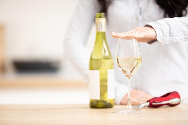 Donna che tiene la mano sopra il bicchiere di vino bianco per esprimere che ne aveva abbastanza.