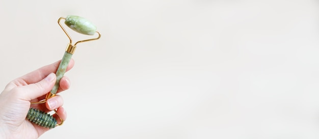 Donna che tiene in mano massaggio rullo di quarzo per il viso di nefrite naturale su sfondo beige