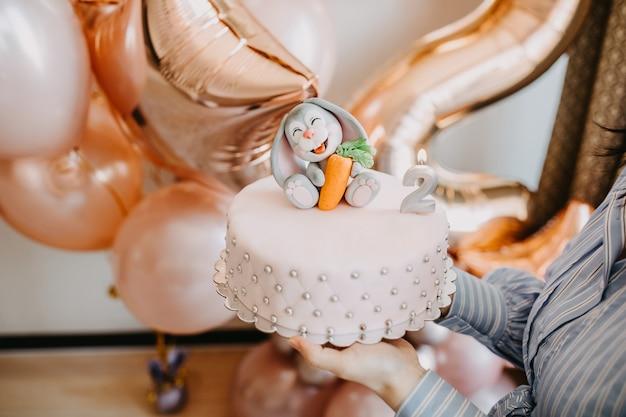 Donna che tiene una torta fatta a mano con decorazioni di marzapane e una candela