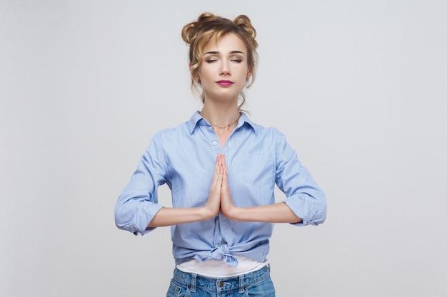 Donna che si tiene per mano in namaste o in preghiera, tenendo gli occhi chiusi mentre pratica lo yoga e medita a casa da sola, con uno sguardo calmo sul viso. foto in studio