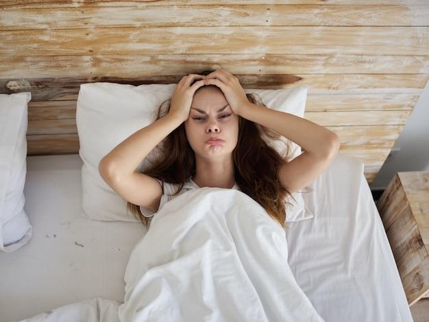 La donna che si tiene per mano ha versato buffonate sdraiata a letto la mattina
