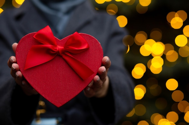 Donna che tiene una confezione regalo di san valentino a forma di cuore con un fiocco su uno sfondo di luci sfocate. primo piano