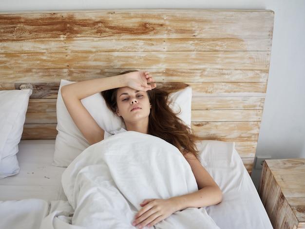 Donna che si tiene la mano sulla fronte sdraiata a letto e non si sente bene. foto di alta qualità