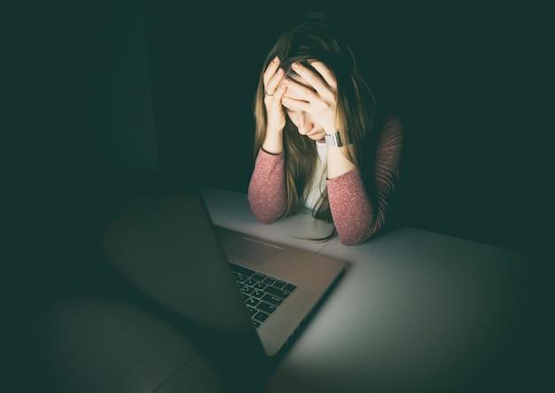 Donna che tiene la sua testa con le mani che si siedono al computer portatile
