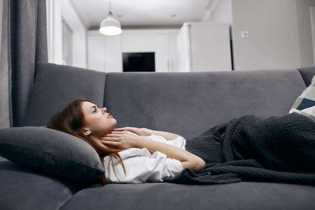 Donna che tiene il suo collo mentre giaceva sul divano che si nasconde con una coperta