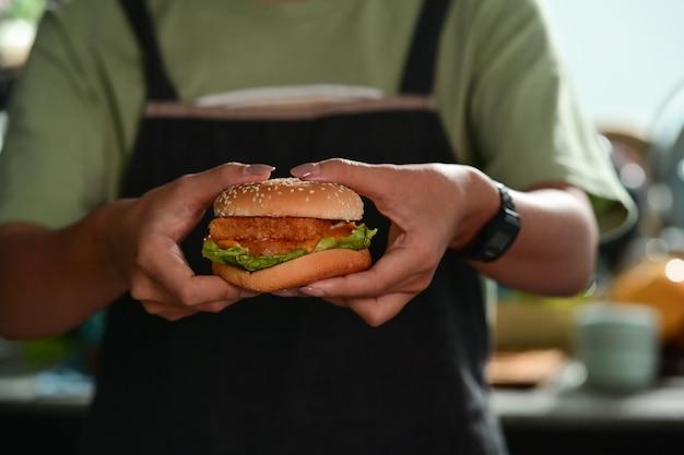 Donna che tiene in mano hamburger fatti in casa.