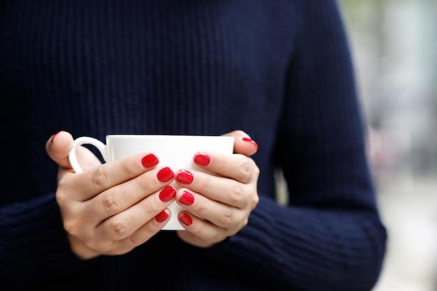 Una donna con una tazza di caffè caldo al bar