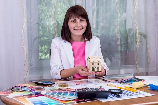 Modello di casa della holding della donna in palme sopra i disegni