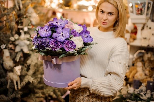 Donna che tiene una scatola enorme con fiori viola e viola decorati con rami di abete