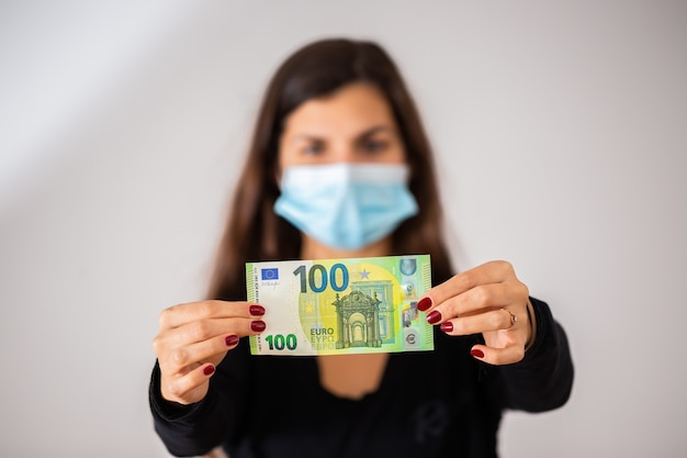 Donna che tiene una banconota da cento euro nelle sue mani e indossa una maschera chirurgica