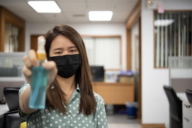 Donna che tiene il barattolo igienico del gel e che indossa maschera