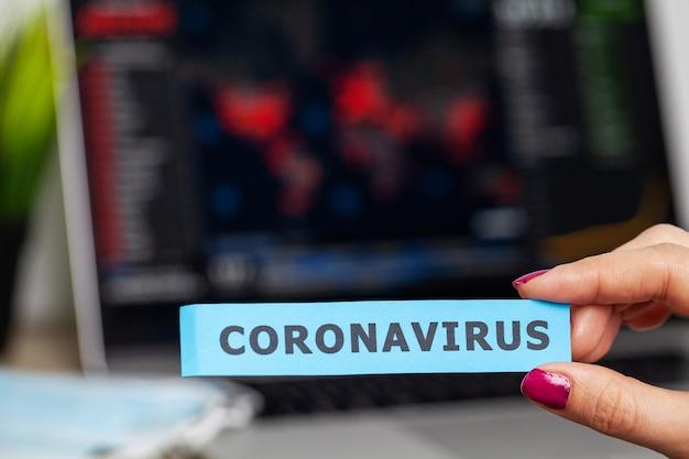 Donna che tiene la scritta covid-19 sullo sfondo della mappa del virus diffusa nel mondo
