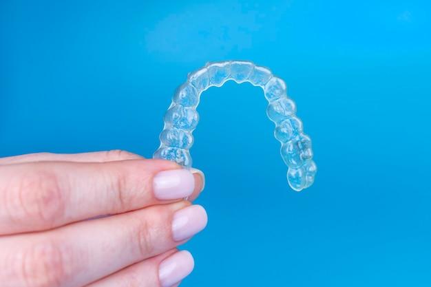 Donna che tiene allineatore trasparente invisibile invisalign o bretelle ortodontiche in plastica