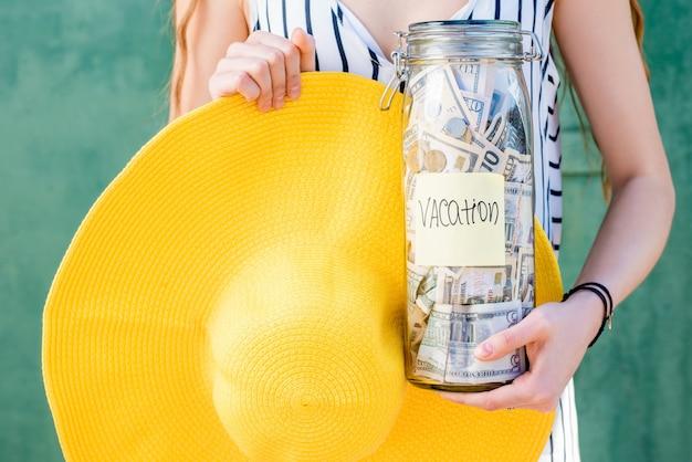 Donna che tiene un barattolo pieno di risparmi di denaro per le vacanze estive con cappello giallo sullo sfondo verde