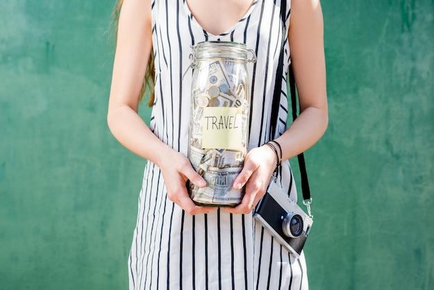 Donna che tiene un barattolo pieno di soldi per viaggiare in piedi con la macchina fotografica sullo sfondo verde. risparmio di denaro per il concetto di vacanza estiva