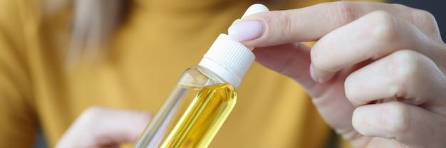 Donna che mantiene un barattolo di olio per capelli nelle sue mani primo piano
