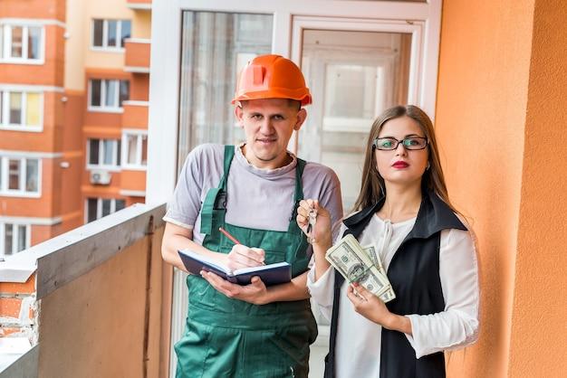 Donna che tiene chiavi e dollari e ordina la ristrutturazione in appartamento