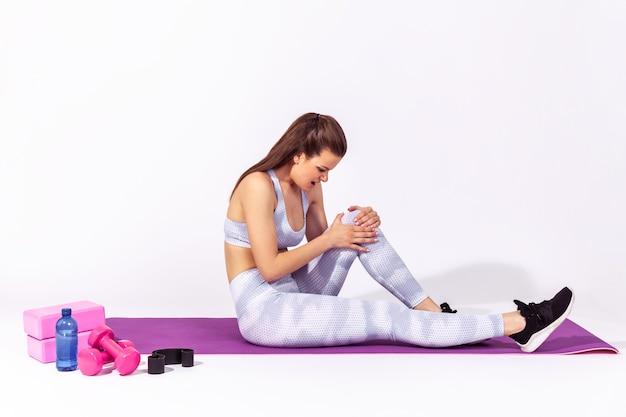 Donna che tiene il ginocchio seduta su un tappetino di gomma, sente dolore, gamba ferita durante l'allenamento