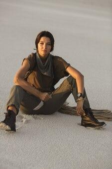 Donna che tiene un coltello all'aperto nel deserto. giovane ragazza pericolosa brutale con un'arma
