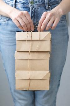 Donna con scatole di cartone kraft consegna cibo o abbigliamento modi moderni per acquistare cibo con consegna