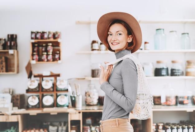 Donna che tiene un grande barattolo di vetro con generi alimentari in un negozio di alimentari senza plastica negozio di rifiuti zero