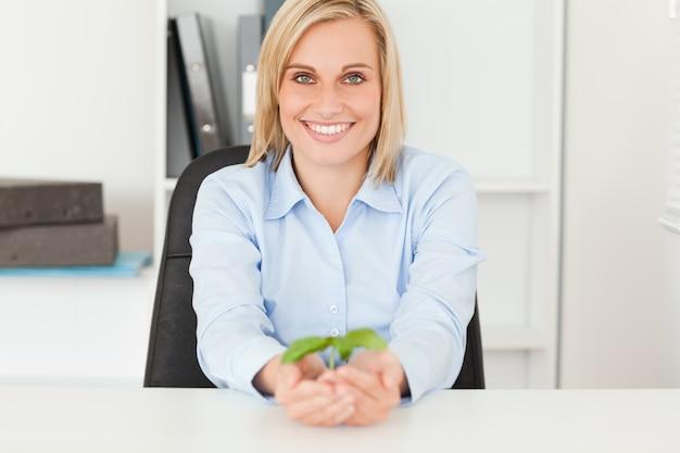 Donna che tiene un piccolo smiies della pianta nella macchina fotografica
