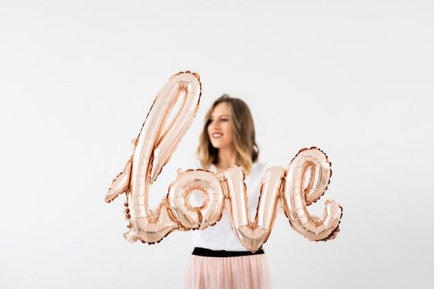Donna che tiene un palloncino foil dell'amore