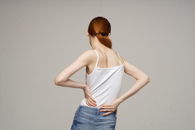 Donna che tiene la medicina di problemi di salute della parte inferiore della schiena