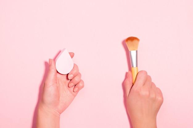 Donna che tiene la spazzola per il trucco e il frullatore di bellezza su sfondo rosa pastello. accessori di bellezza con pennello da trucco contro spugna di bellezza per fondotinta. bellezza piatta, vista dall'alto, copia spazio