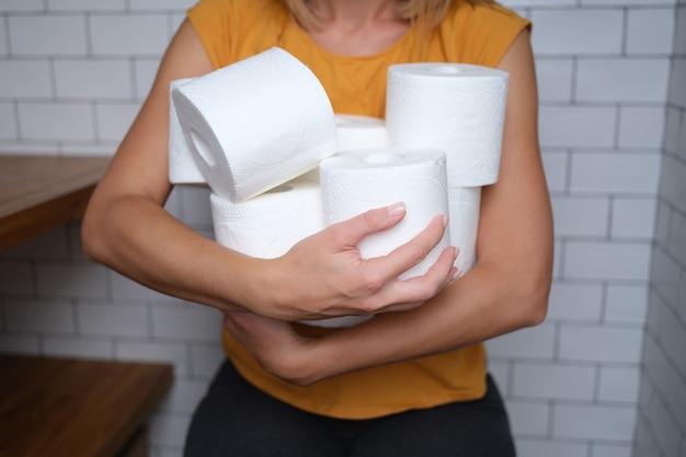 Donna che tiene molti rotoli di carta igienica in bagno. scegliere la carta igienica per il concetto di casa