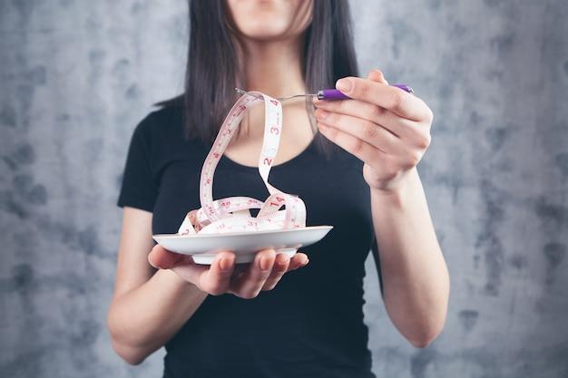 Donna che tiene un metro a nastro con una forchetta