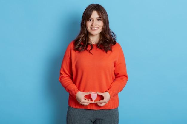 Donna che mantiene la coppetta mestruale davanti alla pancia e guardando sorridendo direttamente alla telecamera