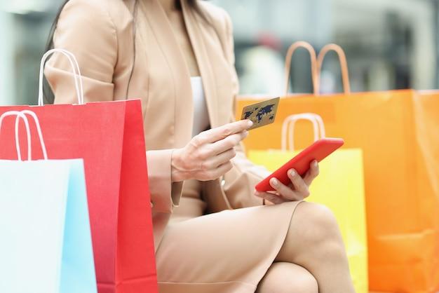 Donna che tiene il telefono cellulare e la carta bancaria di credito vicino al primo piano multicolore delle borse della spesa