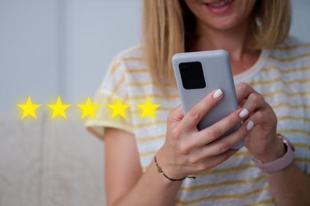 Donna che tiene il telefono cellulare in mano e dà una valutazione a cinque stelle per la qualità dei servizi in primo piano