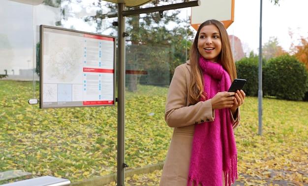 Donna che tiene il telefono cellulare guarda l'autobus arrivare alla fermata dell'autobus