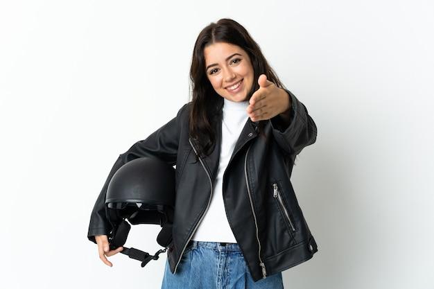 Donna che tiene un casco del motociclo isolato sul muro bianco che agitano le mani per chiudere un buon affare