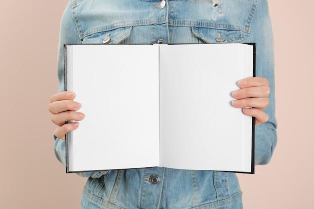 Donna che tiene libro aperto con pagine bianche su rosa