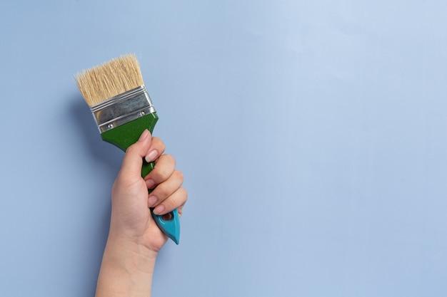 Donna che mantiene il pennello, la festa del lavoro concetto di sfondo