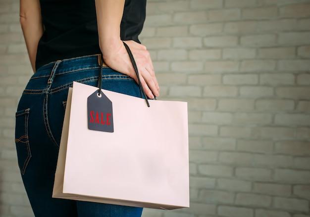 Donna che tiene un sacchetto di carta con l'etichetta del venerdì nero
