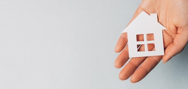 Donna che tiene una casa di carta con le sue mani con il sole su uno spazio azzurro