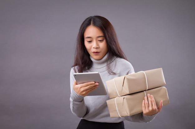 Donna che mantiene la cassetta dei pacchi con tablet computer, concetto di acquisto online