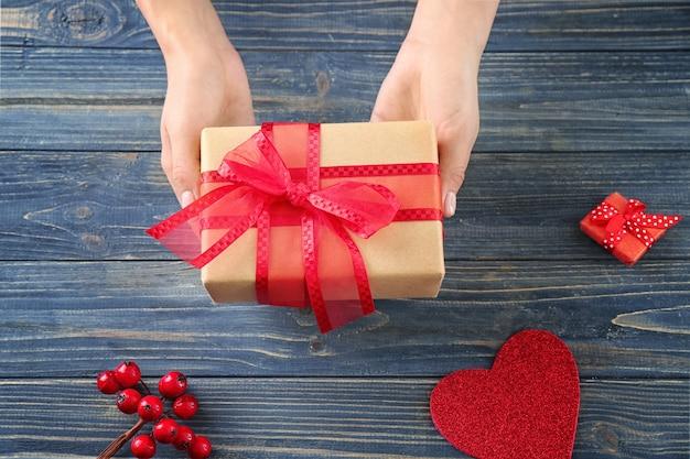 Donna che tiene pacco regalo su tavola di legno, vista dall'alto