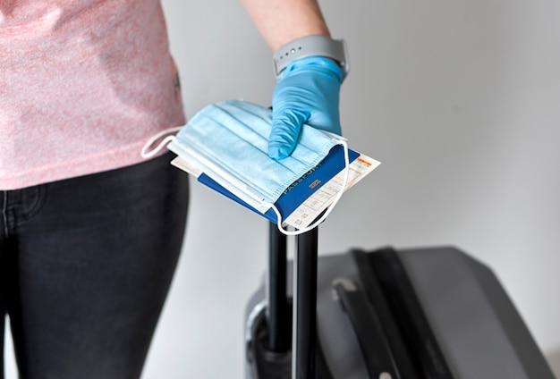 Passaporto della holding della donna con biglietto del treno e mascherina medica
