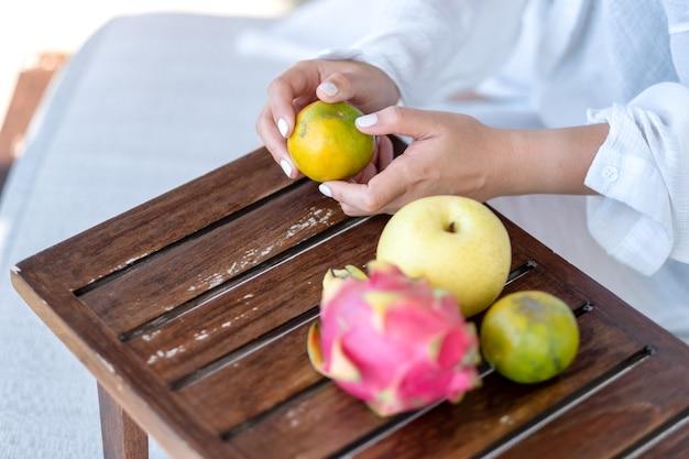 Una donna che tiene e sbuccia un'arancia da mangiare con pera e frutta del drago su un piccolo tavolo di legno
