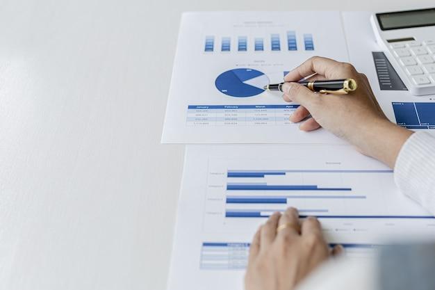 Donna con in mano una penna che punta ai documenti su una scrivania, è una studiosa di finanza, controlla l'accuratezza dei documenti finanziari dell'azienda prima di presentarli ai dirigenti. concetto di audit finanziario.