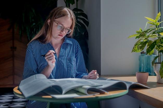 Donna che tiene la penna e legge un mucchio di libri sulla scrivania nel concetto di caffè di ricerca e ricerca di risposte i...