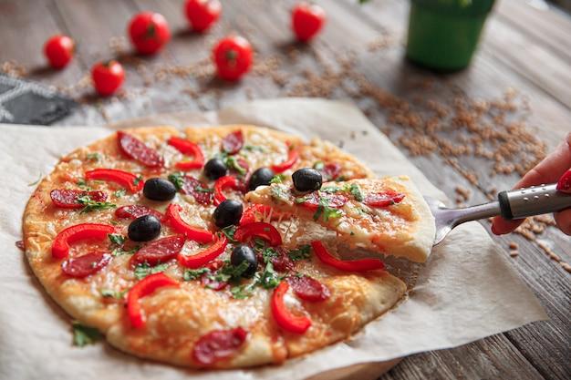 Donna che tiene un pezzo di pizza