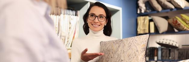Donna che mantiene il cuscino nelle sue mani nel client di officina selezionando tessuto dal catalogo piccolo