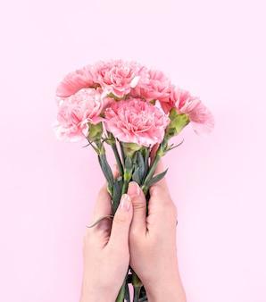 Donna che mantiene garofano rosa su sfondo rosa tabella