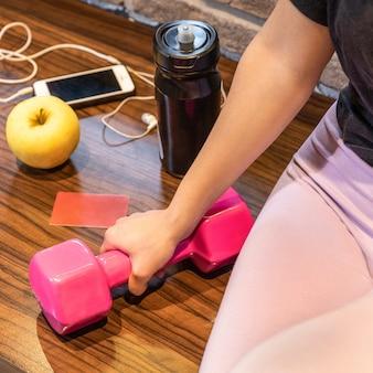 Donna che mantiene il manubrio rosa con la bottiglia di acqua della mela auricolare smartphone